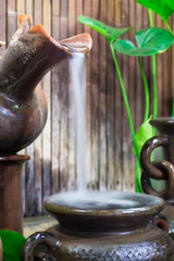 water drop from clay jug in natural garden to thai style antique