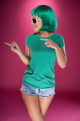 Cute slender young woman with green wig