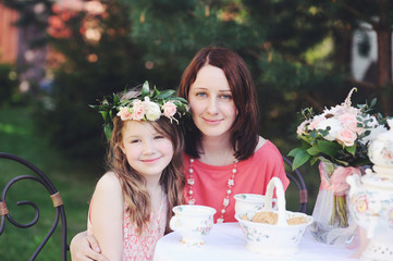 Portrait of mother and daughter at tea table