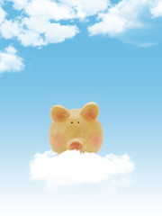 Piggy bank with blue sky and clouds, copy-space