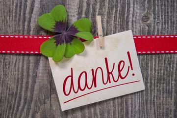 Kleeblatt mit Karte, rotem Band auf Holzhintergrund und DANKE