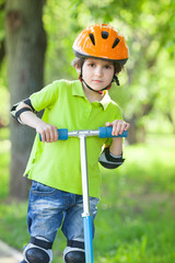 Boy in a safety helmet stands with kick scooter in summer park
