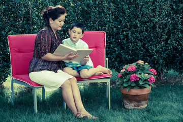 Loving mother is reading book for her son in their garden.