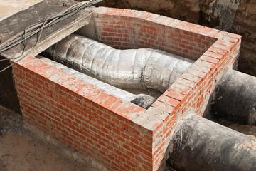 Ein aus Ziegelsteinen gemauerter Schacht für Fernwärmerohre