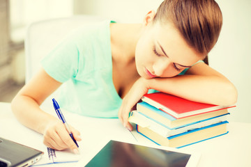 tired student sleeping on stock of books