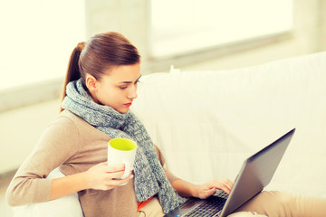 diseased woman in scarf using laptop at home