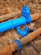 Old big drink water pipes joined with new blue valves and pipes