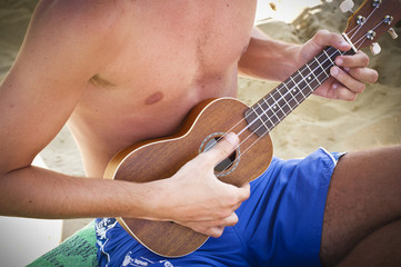 boy playing the ukulele on the beach