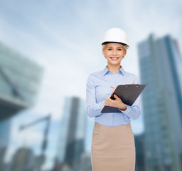 smiling businesswoman in helmet with clipboard