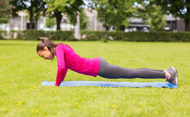 smiling woman doing doing push-ups on mat outdoors