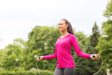 smiling woman exercising with jump-rope outdoors