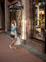 woman with paper bag looking at store window