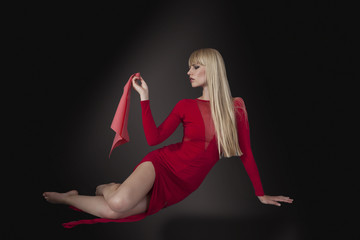 Fashion model in elegant red dress, dark background