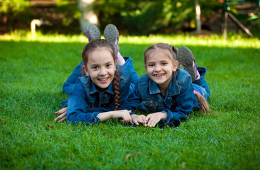 smiling girls using tablet while lying on grass at yard