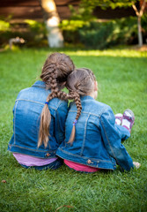 little sisters sitting on grass head to head with joint braids
