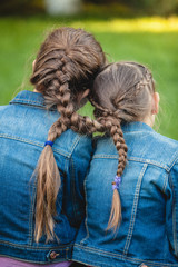 two twins with tied long braids