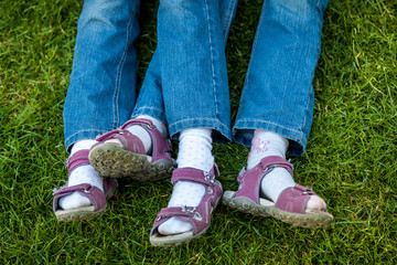 similar legs in sandals of twin girls