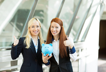 Two business women holding piggy bank giving thumbs up