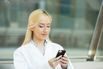 Happy female medical doctor texting on smart phone
