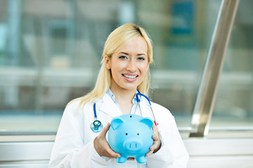 Happy health care professional, doctor, nurse holding piggy bank