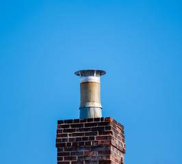 Dark brick chimney and filter on blue sky.