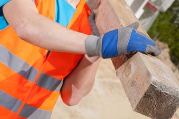 Blue-collar worker holding a wooden beam