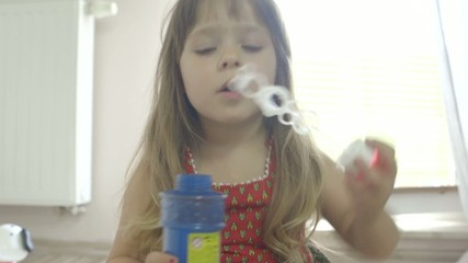 Cute little girl having fun and making soap bubbles at home