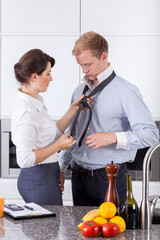 Busy woman tying husband's tie
