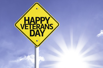 Happy Veterans Day road sign with sun background