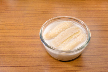 Banana in coconut milk on wooden table,Thai traditional dessert