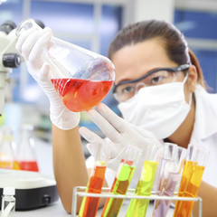 Chemist holding sample of liquid in lab or laboratory