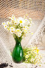 chamomiles in a green vase still life