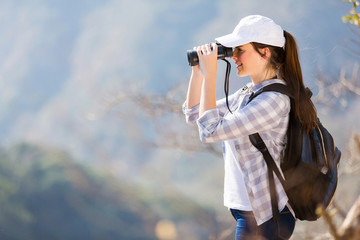 young hiker using binoculars on top of the mountain