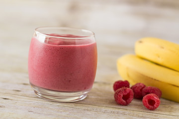 Banana Raspberry Smoothie in Clear Glass on Wood Backdrop