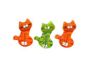 Three wooden cat figure brightly painted in orange and green