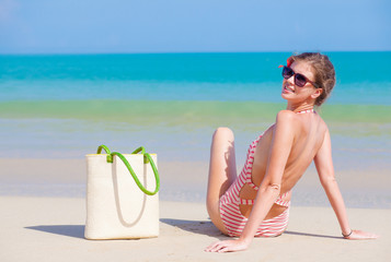 back view of a woman in stripy swimsuit with beach bag at