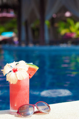 tropical cocktail and sunglasses by pool. party