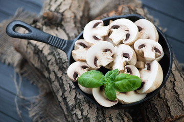 Raw sliced champignons in a frying pan, high angle view