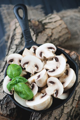 Frying pan with raw champignons on wooden logs, high angle view