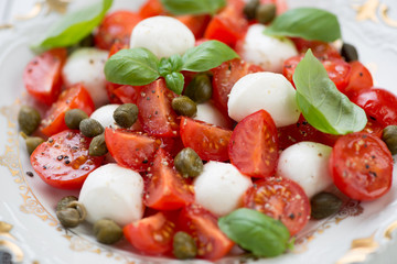 Close-up of caprese salad with capers, horizontal shot
