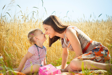 Happy young mother with little daughter on field in summer day