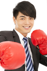 smiling young businessman with boxing gloves