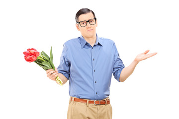 Displeased young man holding a bunch of flowers