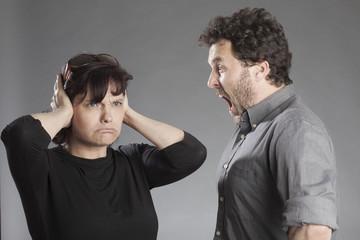 Mann schreit, Frau hält Ohren zu