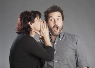 Frau flüstert ins Ohr, Mann überrascht