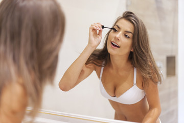 Brunette woman preparing makeup in bathroom