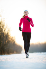 Winter running - Young woman running outdoors on a cold winter