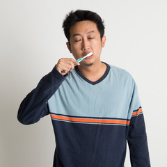 Asian male brushing teeth