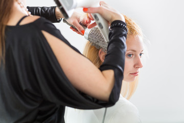 Hairdresser/Hairstyle artist working on a young woman's hair