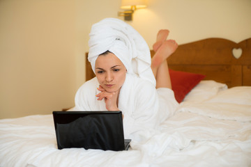 Beautiful woman in bathrobe with laptop